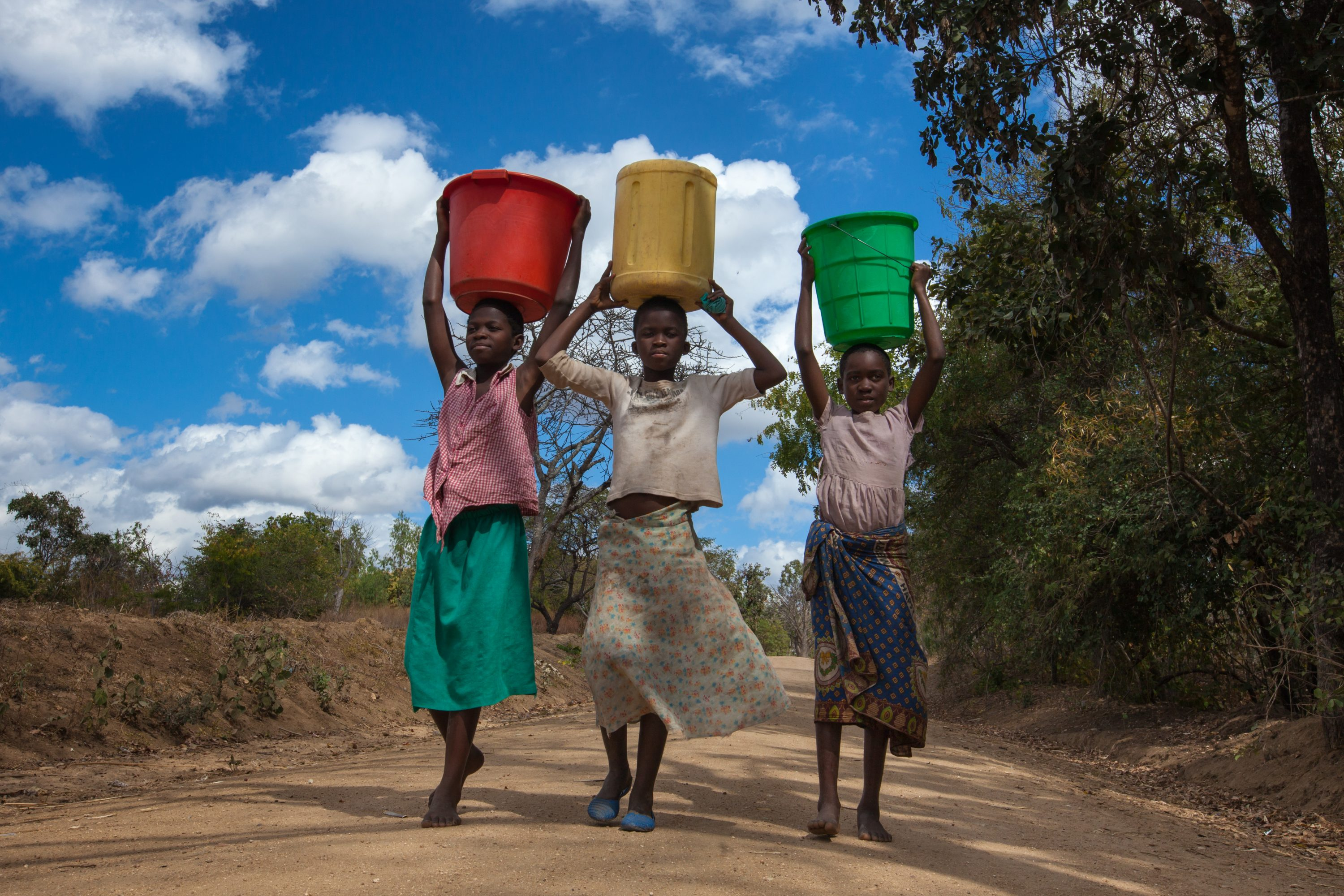 Three Teenage Girls Carrying Colorful Buckets Of Water On A Dirt Road, Returning From Their Journey To The Nearest Borehole, In Balaka District, Southern Malawi, Under A Blue Sky With Clouds.