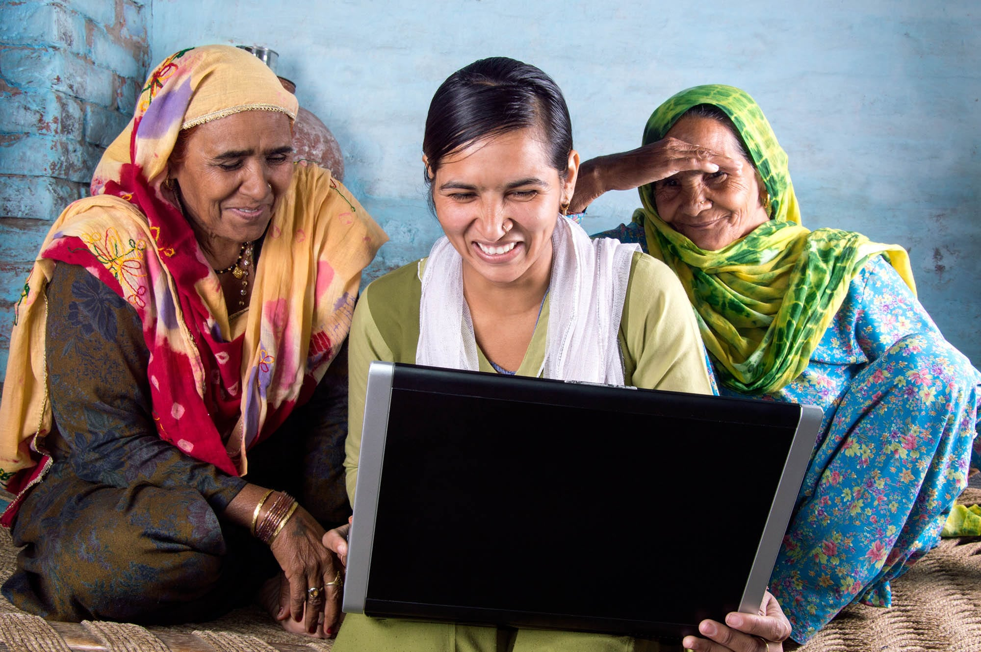 Confident  Rural Indian Young Girl Holding Laptop With Two Senior Women. They All Are Smiling While Holding Laptop.
