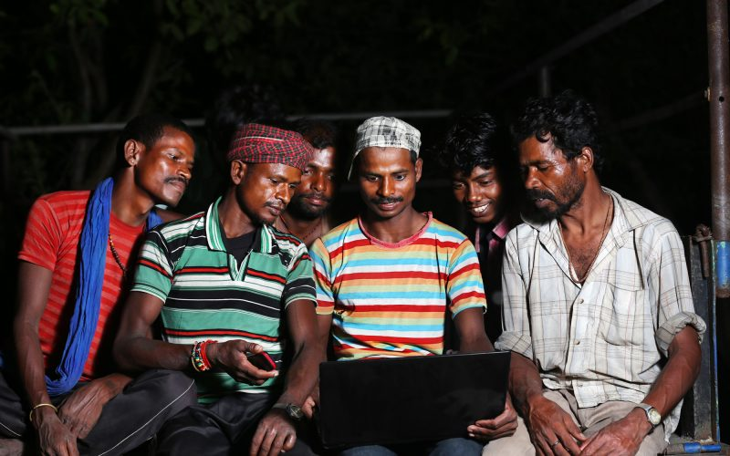 Group of Rural people using laptop in the Night wearing casual clothing and watching inside the Laptop Screen. Some People are Looking Serious and Some People are Smiling while using Laptop, The Shot is taken using Studio Lights.