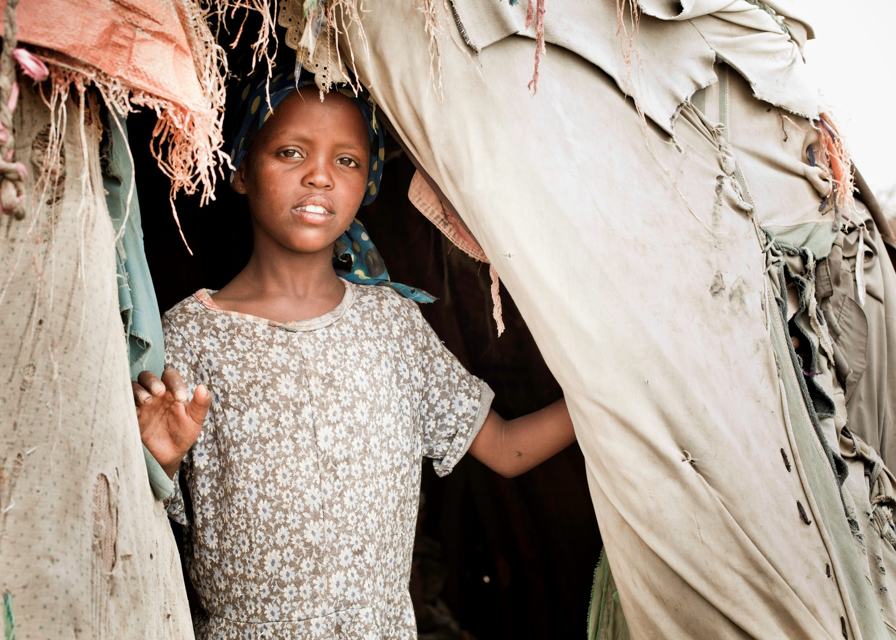 Young Somali Girl Looks At The Camera Through The Open Flap Of Her Cloth Hut.