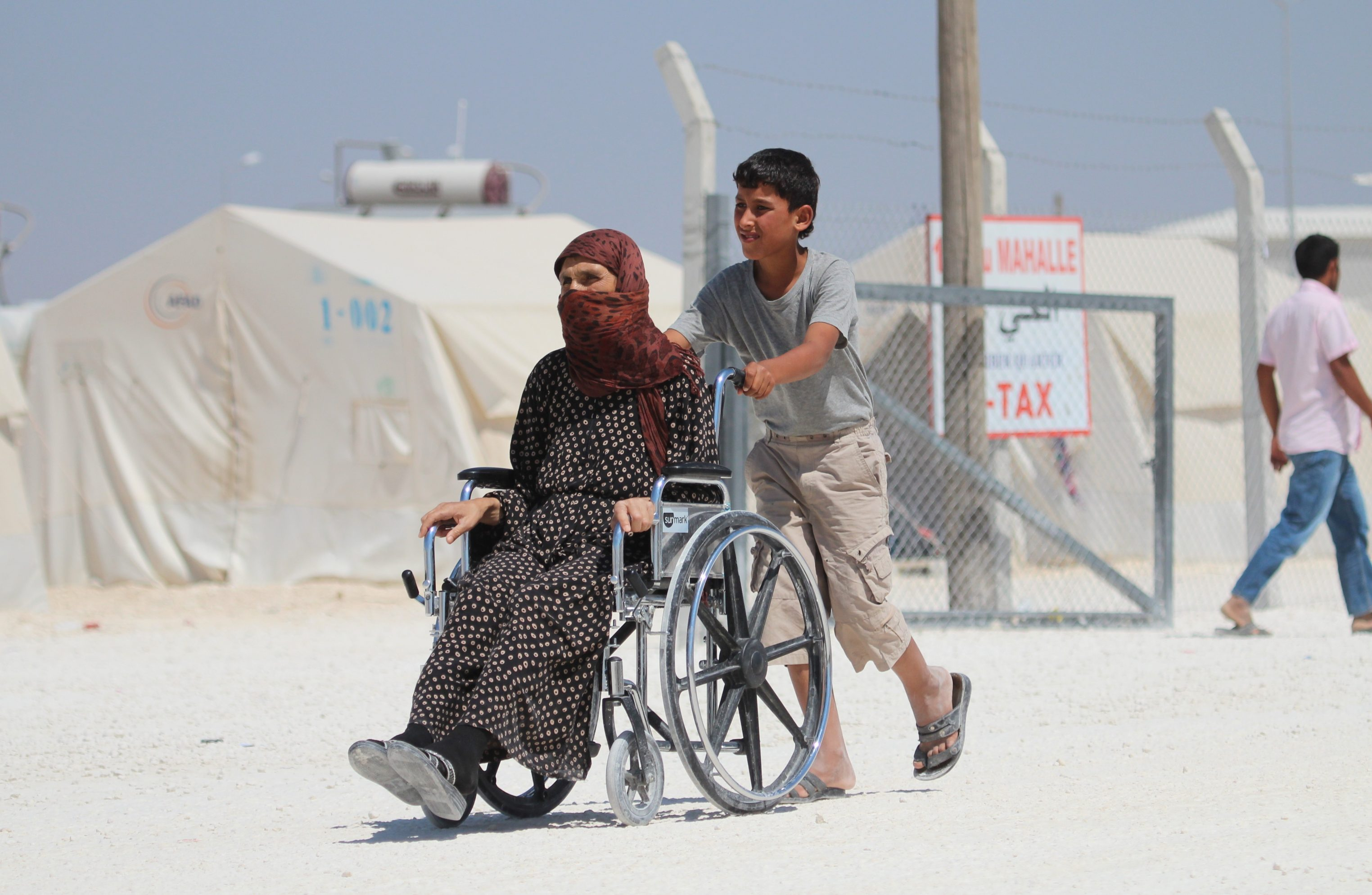 SANLIURFA, TURKEY - JULY 14: A Syrian Boy Helps A Disabled Elderly Woman As He Pushes Her Wheelchair Along A Road At A Refugee Camp In Suruc District Of Sanliurfa On July 14, 2015, As The Syrian Kurds Who Fled The Clashes Between Daesh And Kurdish Armed Groups About A Year Ego, Make Preparations For The Eid Al-Fitr Marks The End Of The Muslim Holy Fasting Month Of Ramadan By Preparing Sweets Despite The All Harsh Conditions At The Camp Away From Their Home. (Photo By Halil Fidan/Anadolu Agency/Getty Images)