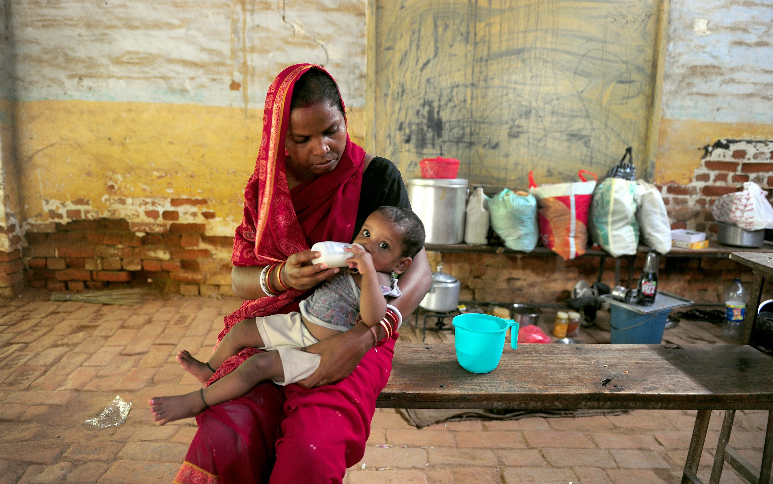A Flood-affected Woman Feeds Her Baby At A Local Shelter In Allahabad On August 4, 2013.  The Monsoon, Which Covers The Subcontinent From June To September And Usually Brings Flooding, Accounts For About 80 Percent Of India's Annual Rainfall.          AFP PHOTO/ SANJAY KANOJIA        (Photo Credit Should Read Sanjay Kanojia/AFP/Getty Images)