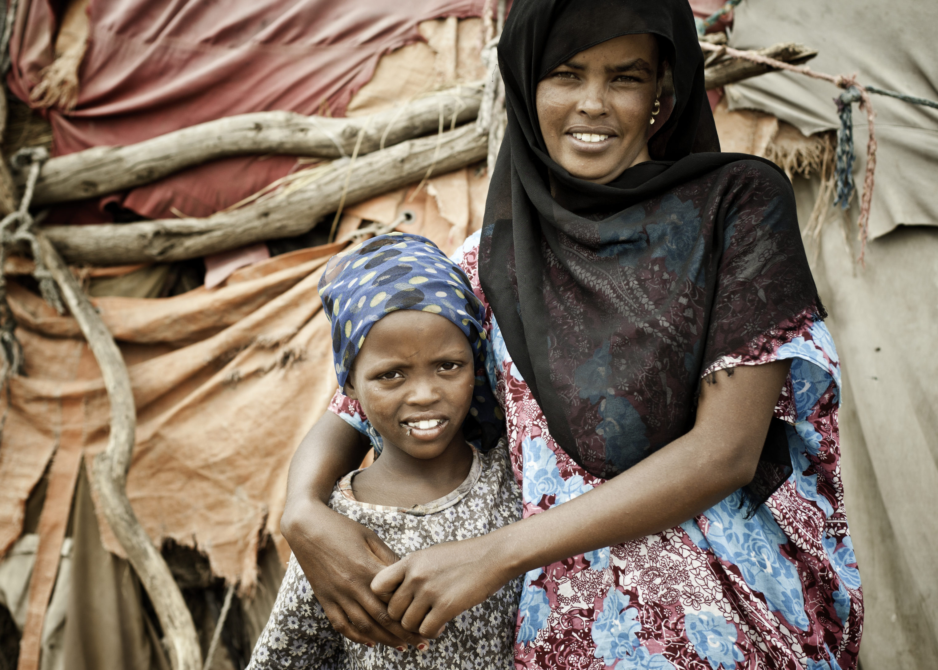 Somali Mother And Daughter Pose For The Camera, Standing In Front Of Their Rustic Home Which Is A Hut Made From Tree Branches And Textiles.